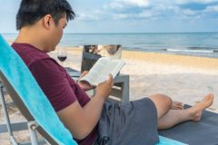 Reading book by laptop , glass of wine relaxing on beach. Man reading by laptop , glass of wine relaxing on beach royalty free stock images
