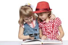 Reading book through the loupe Stock Photos