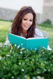 Reading a book lying on the grass Stock Images