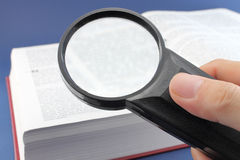 Reading a book with magnifying glass Stock Image
