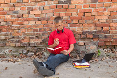 Reading book male student with laptop. Leaning on the bricks wall Royalty Free Stock Image