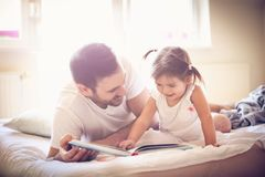 Reading book at morning. Father and daughter. stock photos