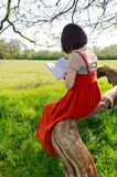Reading a book in nature. A young woman, in a traditional style dress, reading a book and sitting under a tree, with a meadow in the background Royalty Free Stock Photo