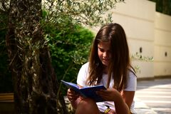 Reading a book near an olive tree