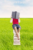 Reading book outdoor. Elementary school student sitting on the stack of books and reads seriously. shot outdoor on the meadow Royalty Free Stock Image
