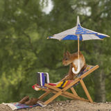 Reading a book. Red squirrel  on a chair holding an umbrella reading a book Royalty Free Stock Photos