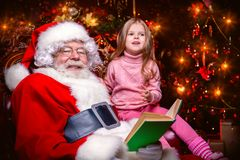 Reading book with santa. A happy young girl is sitting with Santa Claus at home. Merry Christmas and Happy New Year. Miracle time stock image