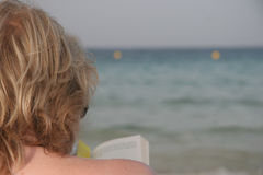 Reading book by sea. Rear view of blond haired woman reading book with sea in background Stock Images
