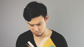 Reading a book seriously. An asian man with black t-shirt royalty free stock image
