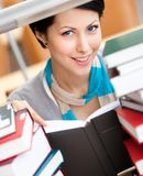 Reading book smiley female student. Reading book female student surrounded with piles of books at the library. Data Royalty Free Stock Photos