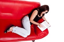 Reading a book on a sofa. Royalty Free Stock Photos