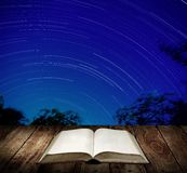 Reading book with star trails background Stock Photography