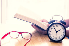 Reading book on table. focus on retro alarm clock. Time to read Royalty Free Stock Photo