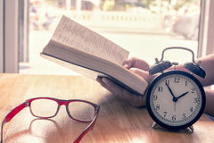 Reading book on table. focus on retro alarm clock. Time to read Royalty Free Stock Images