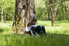 Reading book together. Girls sitting under tree reading a book Royalty Free Stock Photography