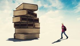 Reading a book on a tower. Student running to a stack of books royalty free stock photo