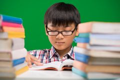 Reading a book. Vietnamese boy in glasses reading a book at the table Stock Photo