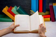 Reading book on white table with another color books on backgrou Royalty Free Stock Photo