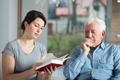 Reading the book. Young attractive caregiver reading the book to aged man Royalty Free Stock Image