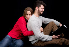 Reading a book. Young men reading a book while his girlfriend is trying to get his attention Royalty Free Stock Photos
