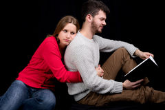 Reading a book. Young men reading a book while his girlfriend is trying to get his attention looking very sad and disappointed Royalty Free Stock Photography