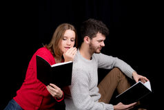 Reading a book. Young men reading a book while his girlfriend is trying to get his attention, whispering in his wear Stock Image