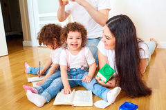 Reading a book with your family. A happy family. Children Twins Stock Photos