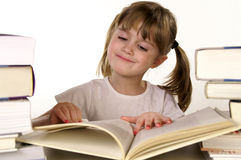 Reading books. A young girl reading a book and smiling royalty free stock photography