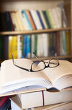 Reading books. Books and glasses on a table in library Royalty Free Stock Image