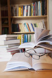 Reading books. Books and glasses on a table in library Stock Photography