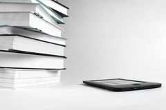 Reading books with an E-book. Stack of books and e-book on white background royalty free stock photo