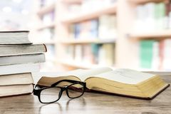 Reading books in the library. Concept image of education and learning - stocks of books next to open book and eyeglasses on a desk in the library Royalty Free Stock Image