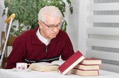 Reading books. Older man with walking stick sitting in his home and reading books Royalty Free Stock Photography