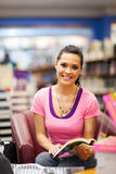 Reading in bookstore. Young woman reading book in bookstore stock photos