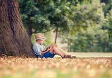 Free Reading Boy Sitting Under Big Tree In Park Stock Image - 68216731