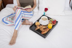 Reading and breakfast on bed Royalty Free Stock Image