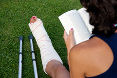 Reading with a broken leg Royalty Free Stock Image
