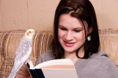 Reading Buddy. Attractive teen girl reading, her pet bird is perched on the book Royalty Free Stock Photo