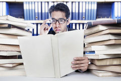 Reading business books. Young businessman reading business books at office Stock Photo