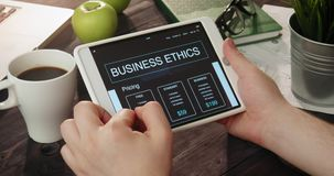 Reading business ethics info using digital tablet stock footage