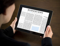 Reading Business News on Tablet PC. Business woman reading business news on the touch screen device Stock Photo