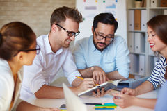 Reading business plan. Multi-ethnic colleagues reading plan in notebook at briefing royalty free stock photos