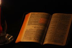 Reading By Candlelight. Holy Bible opened to Gospel of St. Luke, illuminated with a single red candle Royalty Free Stock Photos