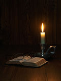 Reading by candlelight. Still life of an old bible and glasses lit by candlelight Stock Image