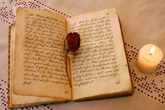 Reading by the Candlelight. Dried red rose on an open old book from the 19th century by the candlelight Royalty Free Stock Image