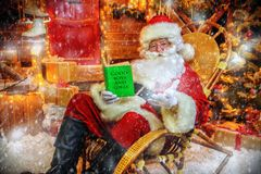 Reading christmas wishes. Santa Claus is preparing for Christmas, he reads a book with children`s desires. House of Santa Claus. Christmas decoration stock images