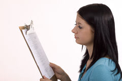 Reading Clipboard. Young woman reading information on clipboard Royalty Free Stock Photography