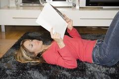Reading comics on her flat Stock Photo
