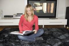 Reading comics on her flat Stock Image