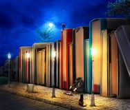 Reading concept. Fantasy. Stack of book as buildings. On a street with streetlight in night. 3d illustration Stock Photos